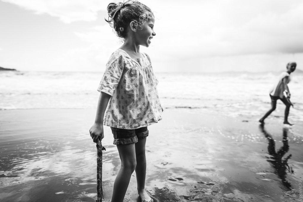 photo grand angle petite fille sur la plage en noir et blanc