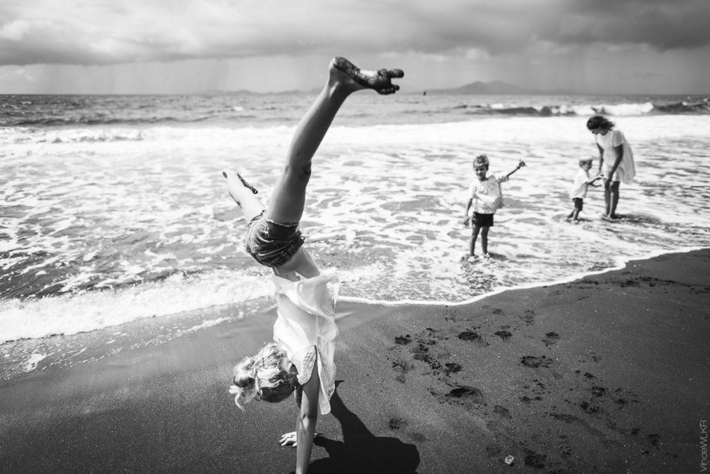 fille qui fait une roue sur la plage en noir et blanc