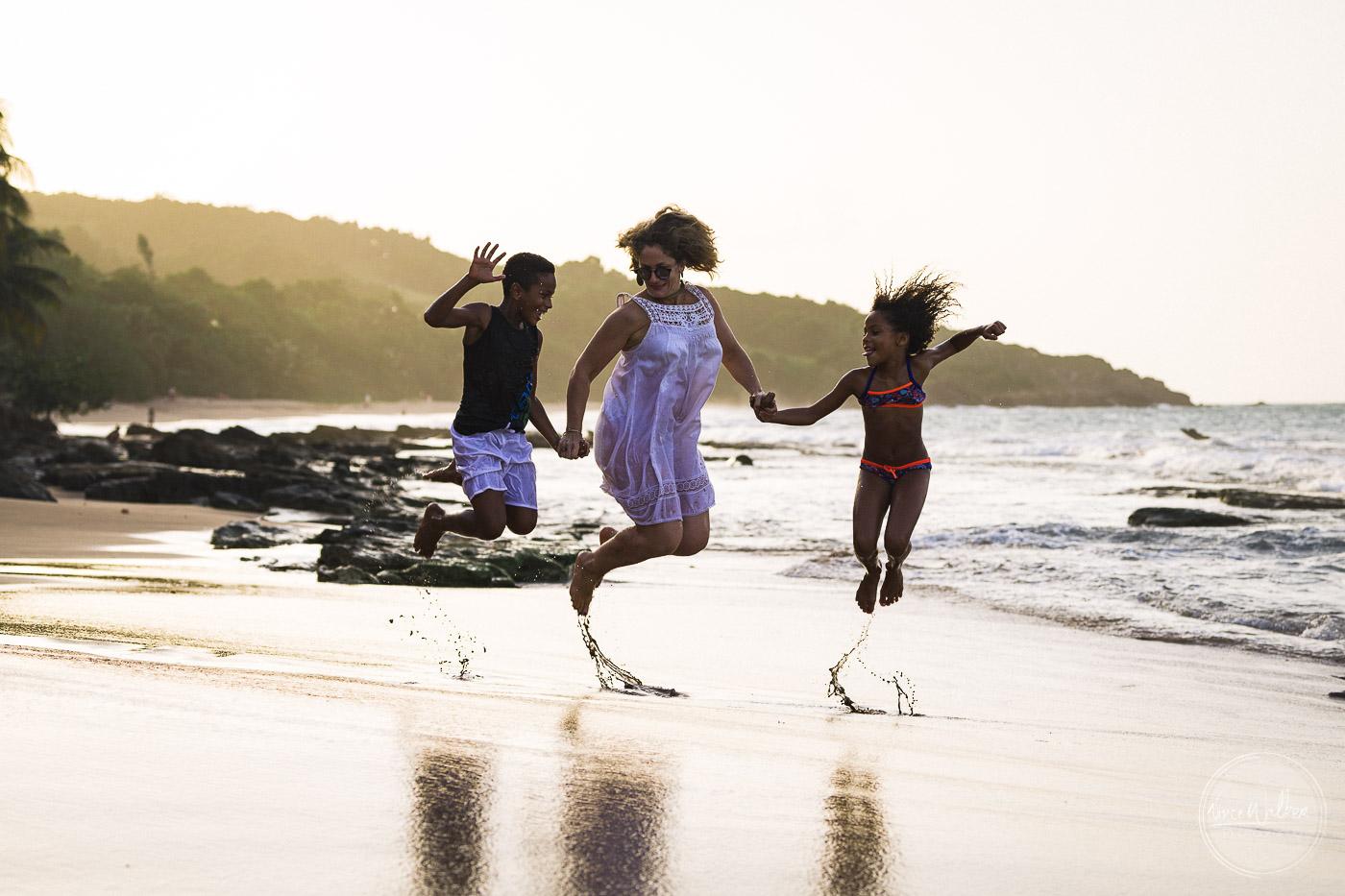 une famille sur une plage de guadeloupe saute en l'air