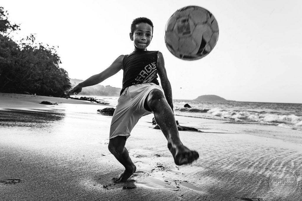 jeune joueur de foot sur la plage
